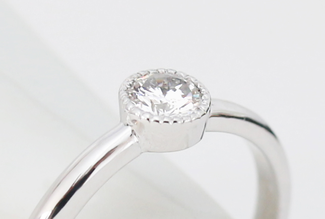 ミル打ちの石枠の婚約指輪